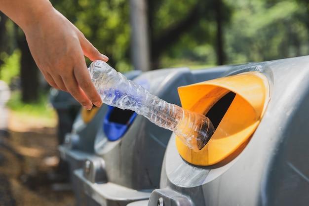 Руки женщины выбрасывают пластиковые бутылки в мусорное ведро.