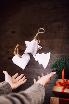 女性の手が自家製のクリスマスツリーのおもちゃを投げる
