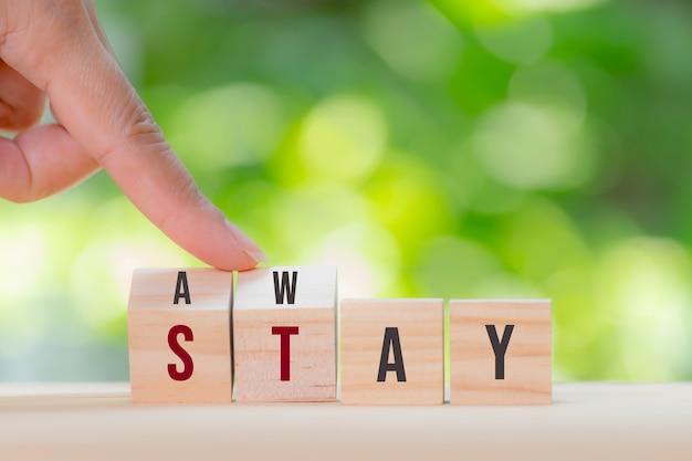 Женщина руками поворачивает деревянный куб, чтобы изменить слова, чтобы остаться. оставайтесь дома, чтобы остановить вспышку covid-19