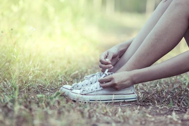 여자 손 공원에서 그녀의 오래 된 신발 매. 빈티지 색조