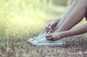 Woman hands tying her old shoes in the park. vintage color tone