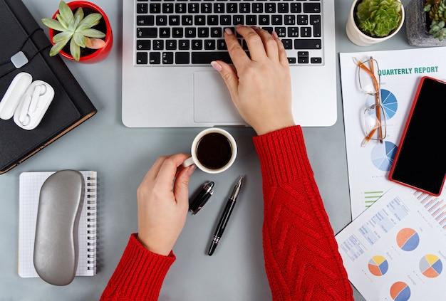 ラップトップで入力し、灰色のオフィスのデスクトップビューでコーヒーを飲む女性の手