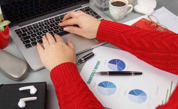 Женщина руки печатает на ноутбуке и пьет кофе на сером офисном столе, вид сверху