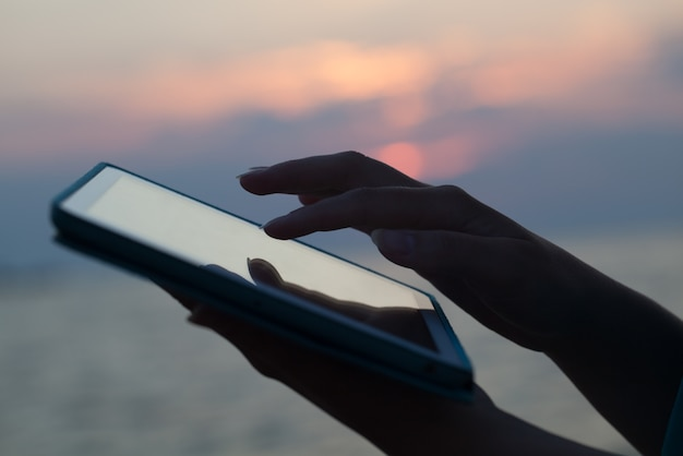 Woman hands typing on pad outdoor at sunset