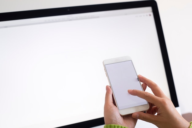 Woman hands using cell phone with laptop