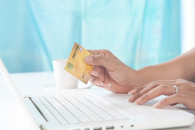 Woman hands using laptop and holding credit card. shopping and lifestyle concept