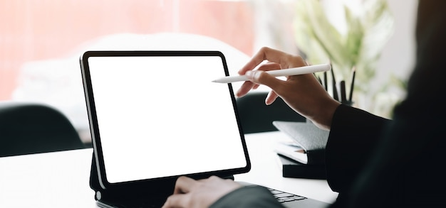 Woman hands using laptop with blank screen at an office desk