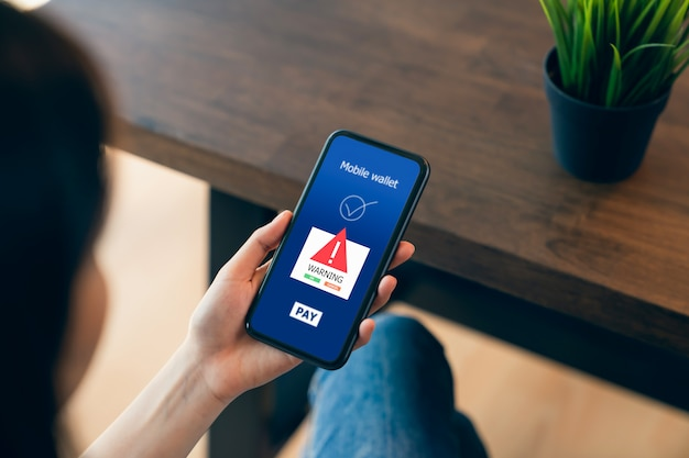 Woman hands using phone and login mobile banking online with show a warning screen of malware dangers.