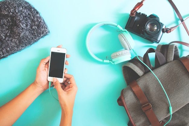Woman hands using smart phone with items for traveler. flat lay. top view