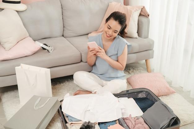 スマートフォンを使用して女性の手が新しい旅のためのアクセサリーを準備するためのチェックリストを書き、スーツケースのバッグに服を詰める