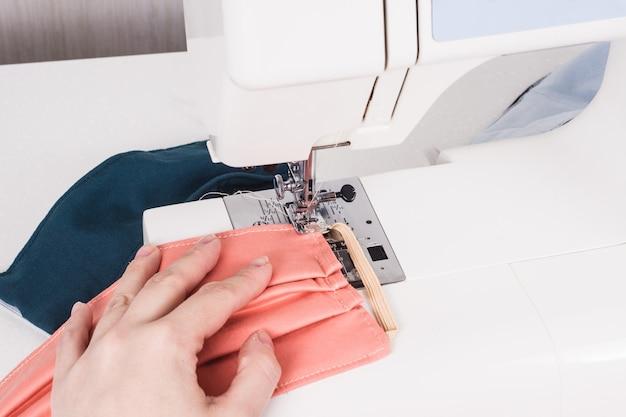 Руки женщины сшивают маску на швейной машине во время пандемии коронавируса.