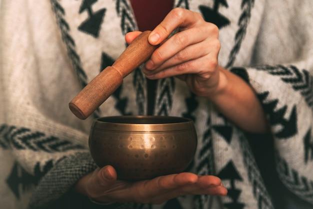 手作りのポンチョを着たチベットのシンギングボウルを使った女性の手コピースペース瞑想