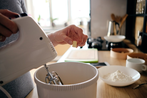 Woman hands using a white handheld mixer