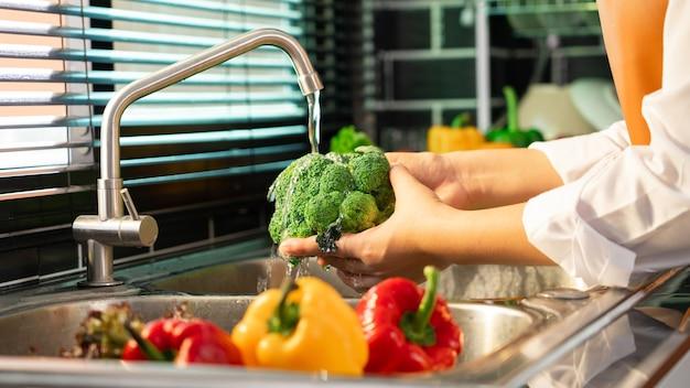 Женщина руки мыть овощи для приготовления веганский салат