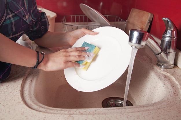 Woman hands washing white plate in kitchen sink