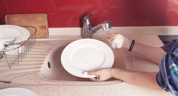 Woman hands washing white plate in kitchen sink.