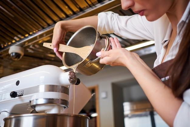 Женщина руки взбивая миксером. приготовление десерта на современной кухне