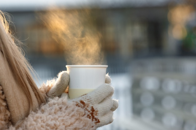 Woman hands in white mittens holding steaming white cup of hot coffee or tea in cold winter sunny day
