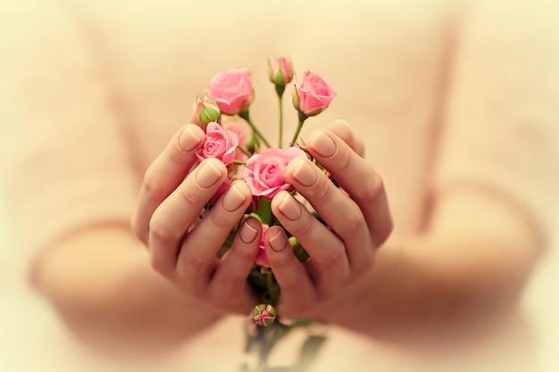 バラの美しい花束を持つ女性の手、クローズアップ