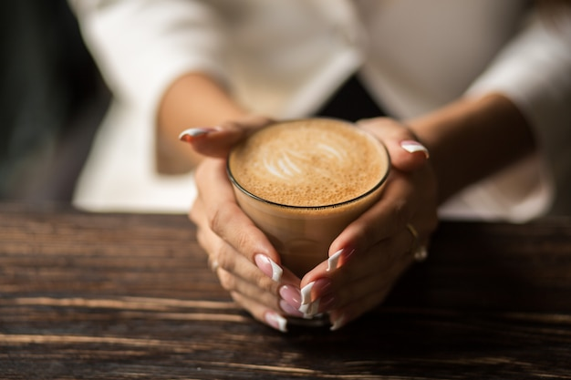 Woman hands with beautiful manicure close-up hold a cup with hot coffee on a wooden table