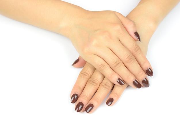 白い表面に美しいマニキュアと女性の手