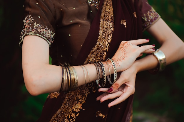 Woman hands with black mehndi tattoo. hands of indian bride woman with black henna tattoos. fashion. india