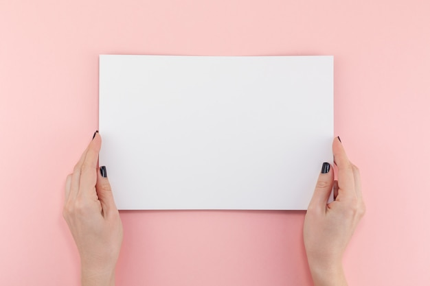 Woman hands with blank a4 paper sheet