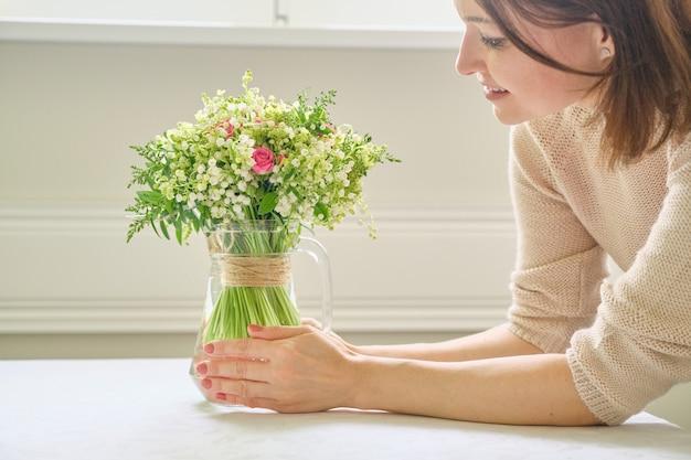 テーブルの上の花瓶に花束と女性の手。スズランとバラの花束、春休み、イースター、母の日を保持している女性