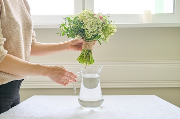 テーブルの上の花瓶に花束と女性の手