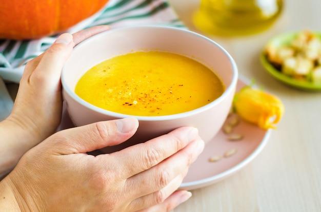 種子とクルトンとおいしいクリーミーなカボチャスープのボウルと女性の手
