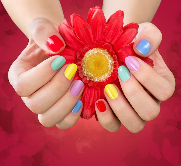 Woman hands with bright manicure and flower, isolated