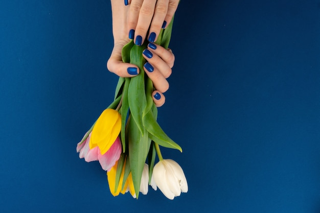 Woman hands with manicure holding colorful tulips