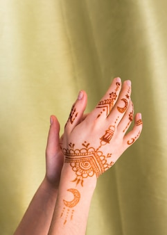 Woman hands with mehndi near textile
