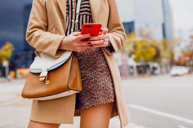 携帯電話で女性の手。おしゃべりベージュのコートでスタイリッシュな女の子。近代的な都市。