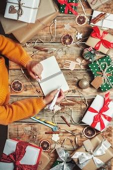 サンタクロースに手紙を書くペンとメモ帳で女性の手