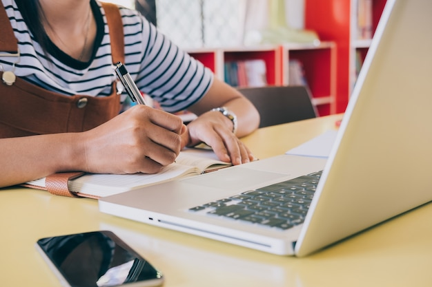 사무실 책상 테이블에 노트북을 쓰는 펜으로 여자 손 클로즈업. 사업 개념.