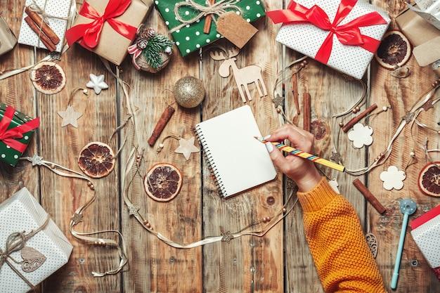 サンタクロースに手紙を書く鉛筆とメモ帳で女性の手