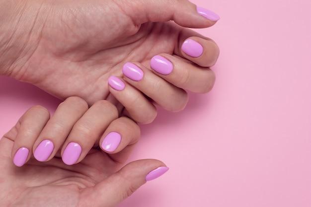 ピンクのマニキュアで女性の手。