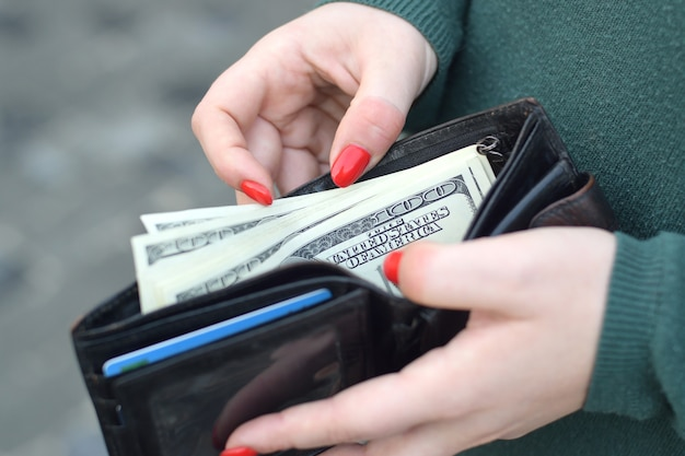 Woman hands with red nails holds black mens purse with many us hundred dollars bills. concept of salary earnings or counting money