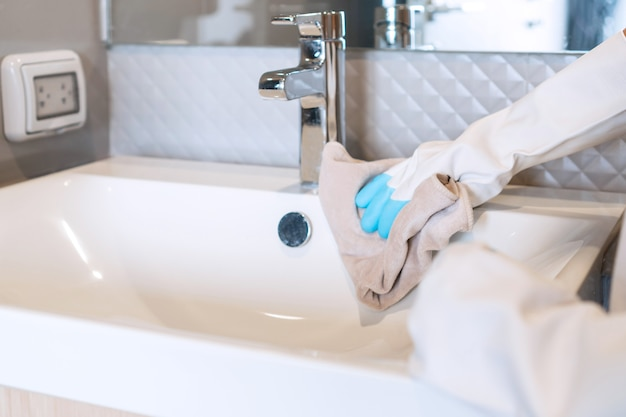 Woman hands with rubber gloves washing and cleaning bathroom at home. closeup