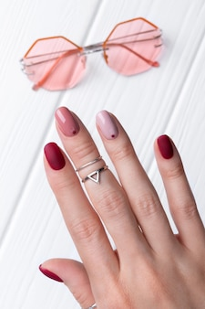 Woman hands with silver jewelry and accessories. woman with minimal pink spring summer manicure design.