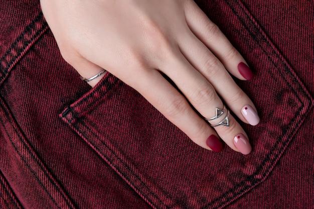 여자 손은 보석 및 액세서리입니다. 최소한의 분홍색 봄 여름 매니큐어 디자인 여자.