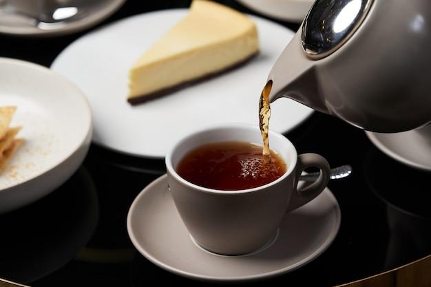 ティーポットカップにお茶を注ぐと女性の手クローズアップ