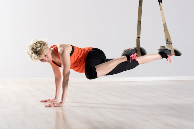 Woman on hands with training trx rings around ankles
