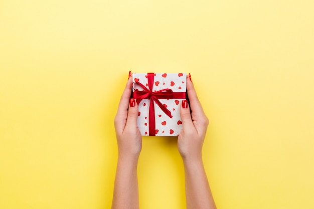 Woman hands with wrapped present with red ribbon