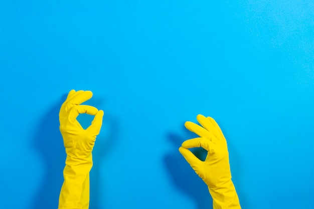 Woman hands with yellow rubber gloves making a gesture meaning on blue background