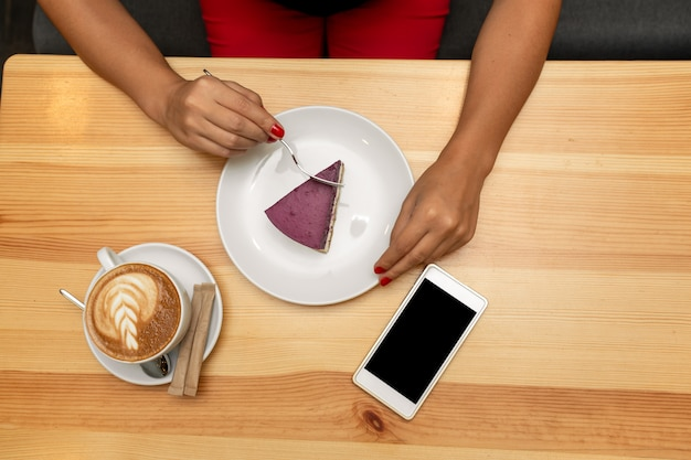 Woman hands on wooden table hold coffe cup near cheesecake and smartphone