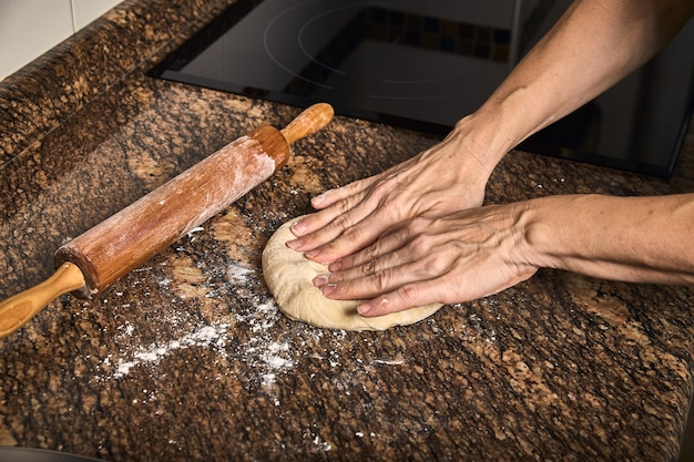 Woman hands working on a dough to cook a tasty pizza