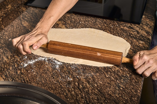 Woman hands working on a pizza dough