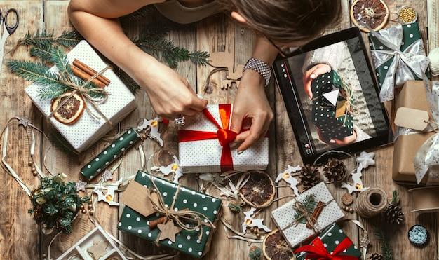 Руки женщины обертывают рождественский подарок с планшетом на столе